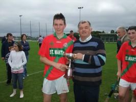 Patrick Brennan captain of u14 team receiving cup from Bord na Nog chairman Joe Pyke